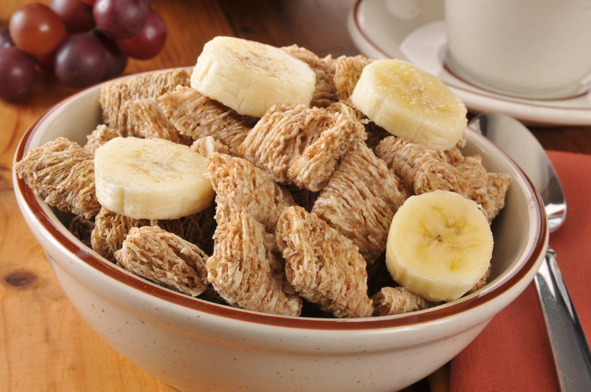 Close-up of a bowl of wheat cereal with banana slices together in a bowl.