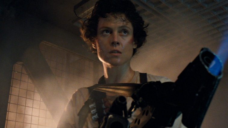 Sigourney Weaver in Aliens stands looking serious holding a machien