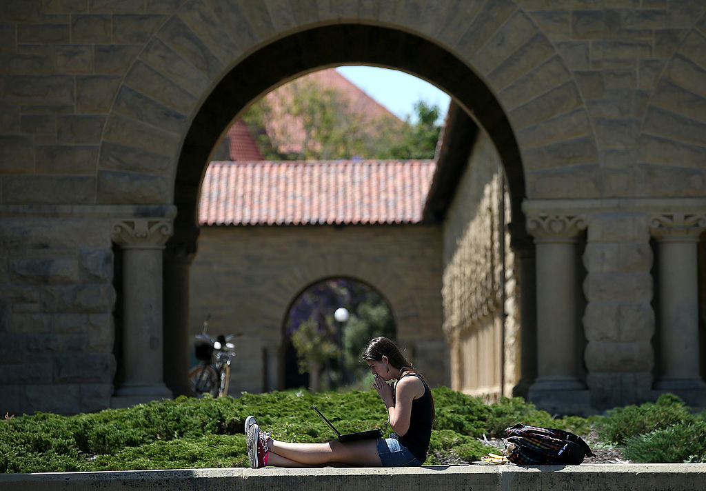 A woman works on a laptop on the Stanford University campus