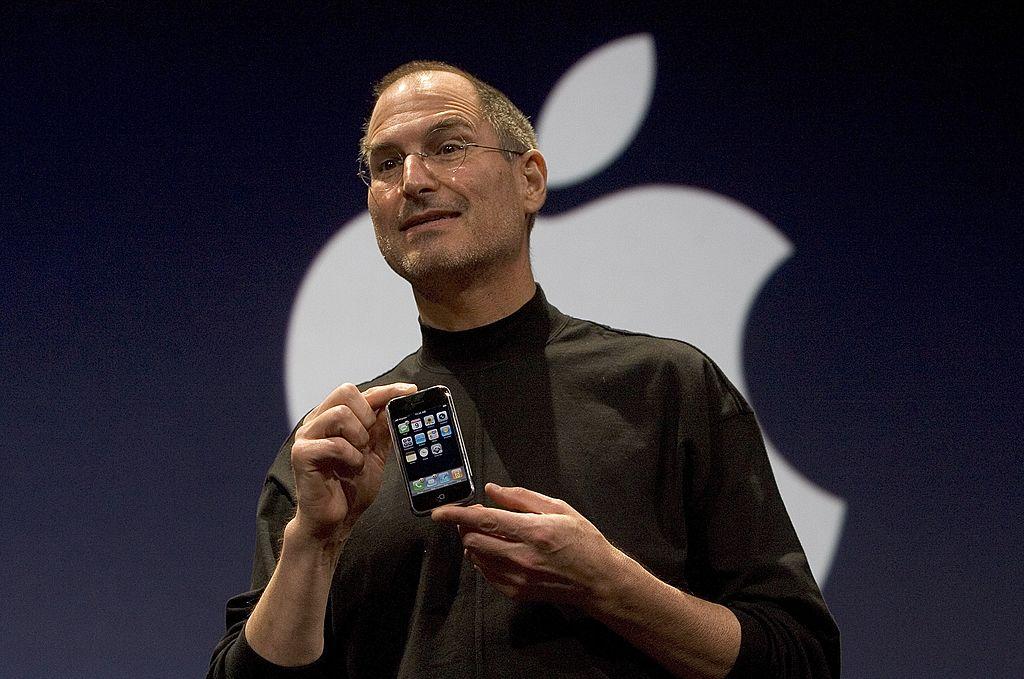 Apple CEO Steve Jobs holds up an iPhone