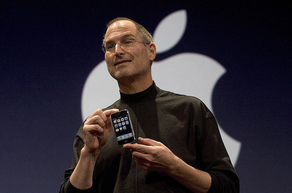 Apple CEO Steve Jobs holds up the iPhone 1