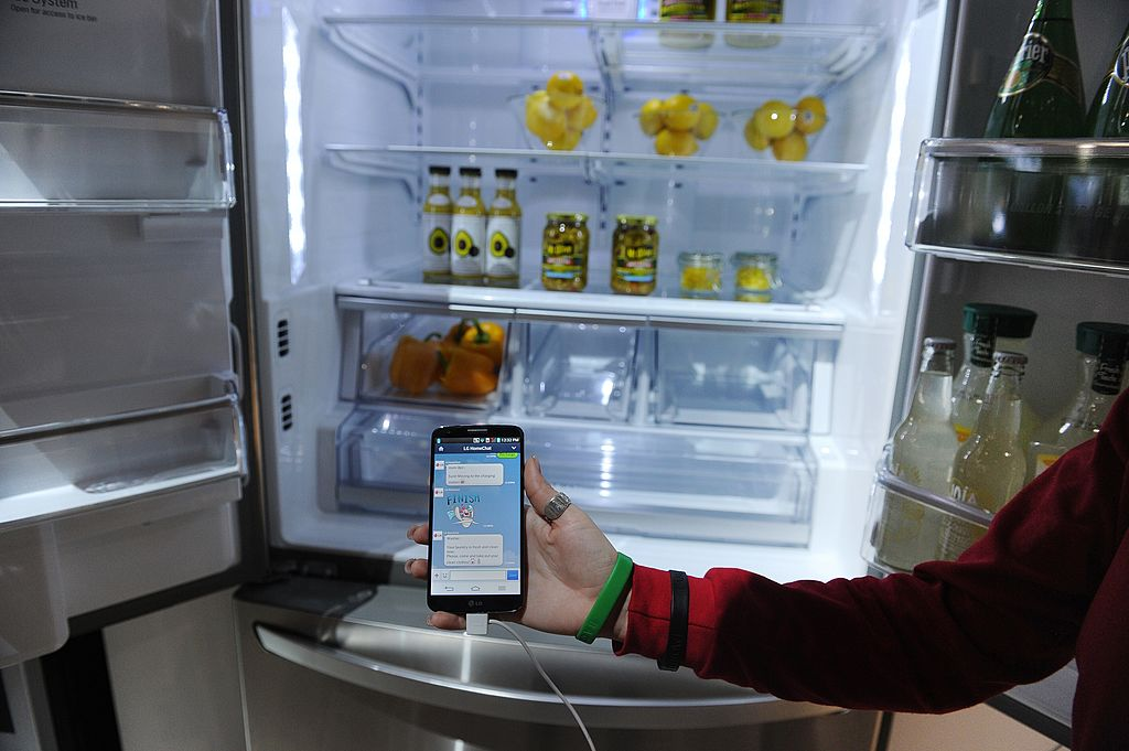 a smartphone with Home Chat in front of an LG smart refrigerator
