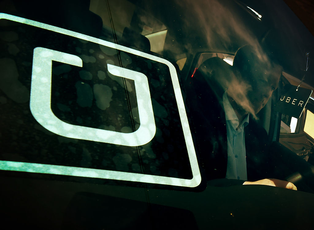 A man checks a vehicle at the first of Uber's 'Work On Demand' recruitment events