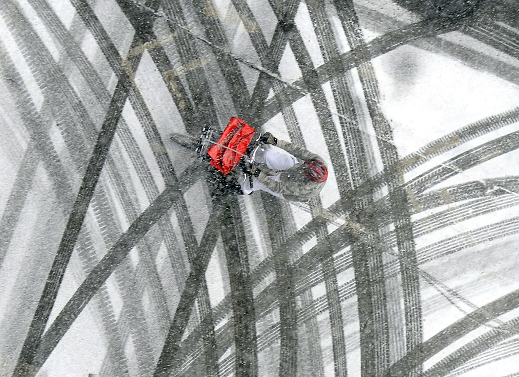 A pizza delivery man rides his bicycle through the snowy streets.