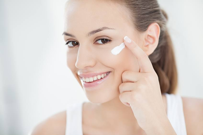 young woman applying face cream