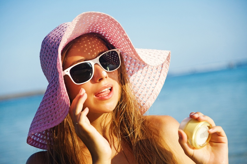Woman wearing hat applying sunscreen