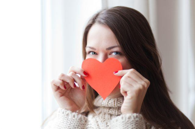 Image of woman holding heart symbol