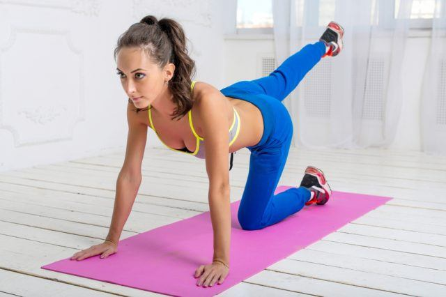 woman with ponytail workout leg swing doing yoga