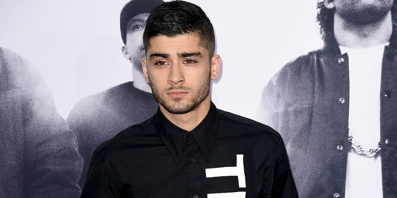 Zayn Malik is wearing a black shirt on the red carpet.