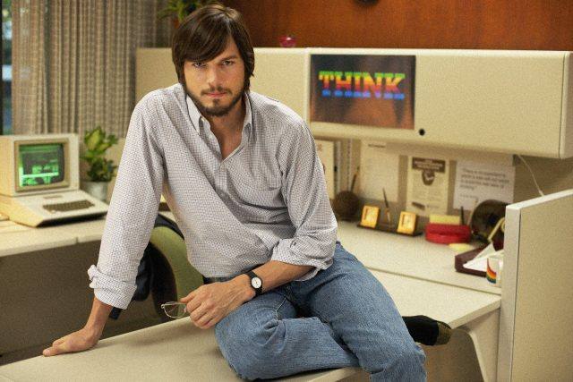 Ashton Kutcher as Steve Jobs sitting on a desk in front of an old computer and a 'THINK' poster in Jobs the film