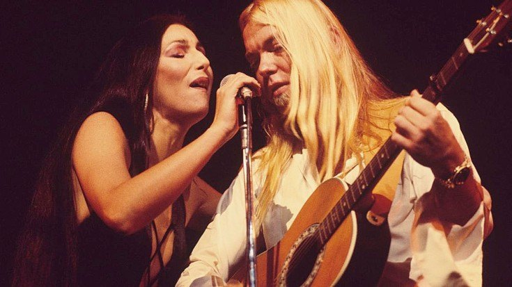 Cher and Gregg Allman singing together in front of a microphone on-stage
