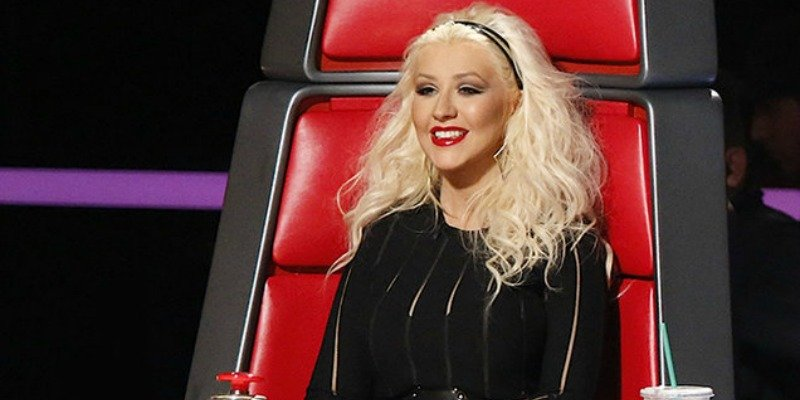Christina Aguilera sitting in the chair and smiling on The Voice