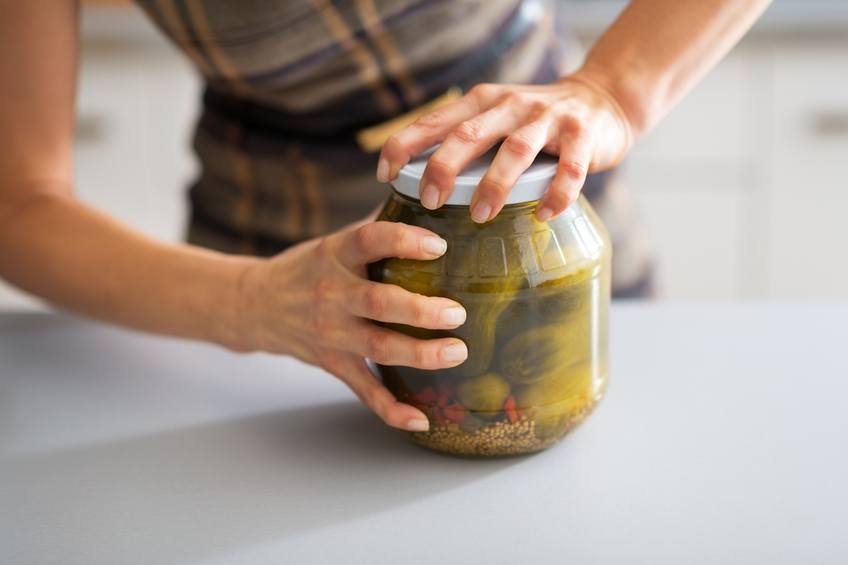 Woman trying to open a jar of pickles.