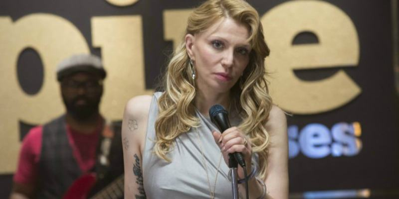 Courtney Love in a white dress, singing into a microphone