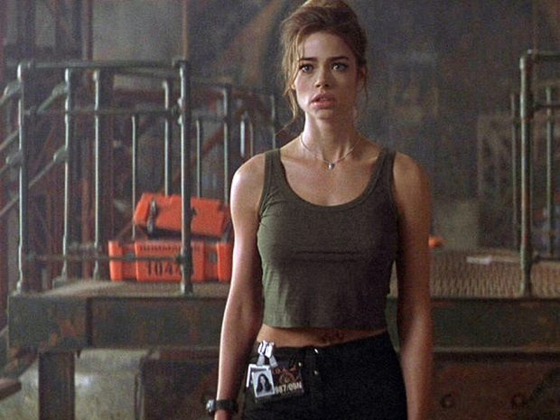 Denise Richards with her hair pulled back looking surprised in a warehouse in 'The World Is Not Enough'