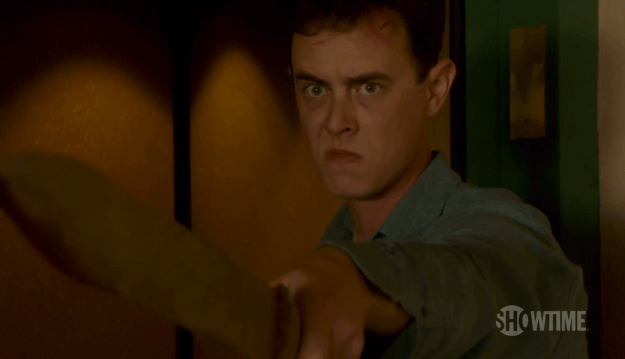 Colin Hanks looks angry holding a wooden sword out in front of him on Dexter
