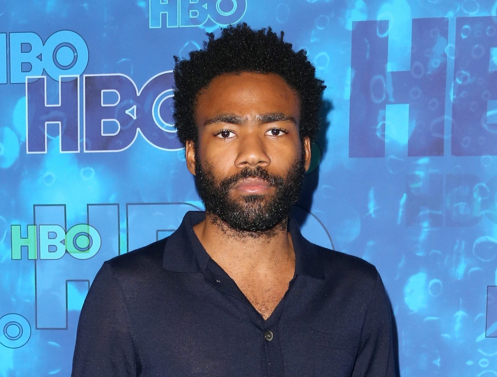 A bearded Donald Glover, looking into the camera in front of an HBO background