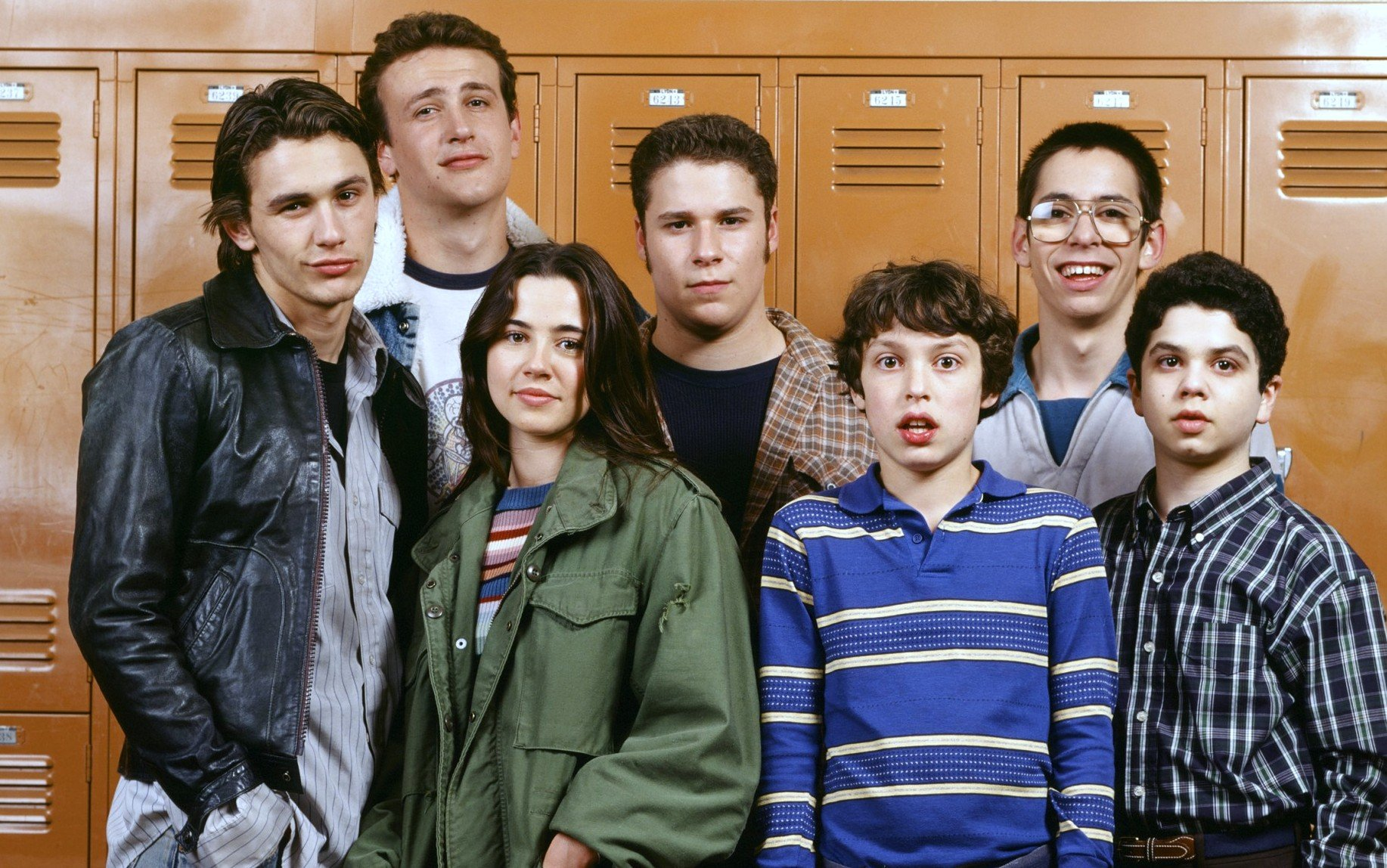 The cast of 'Freaks and Geeks' are standing together in front of orange lockers.