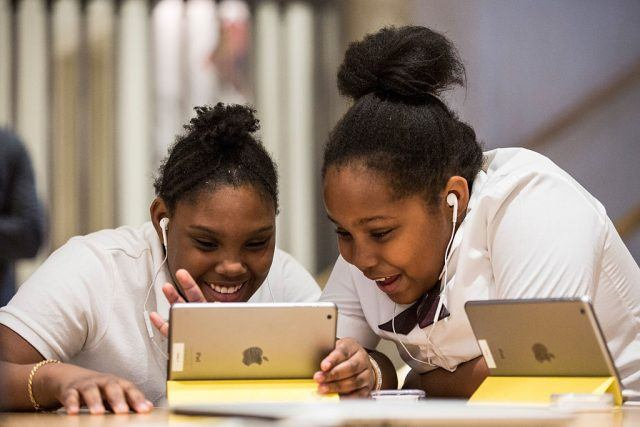 Two young girls playing on an iPad