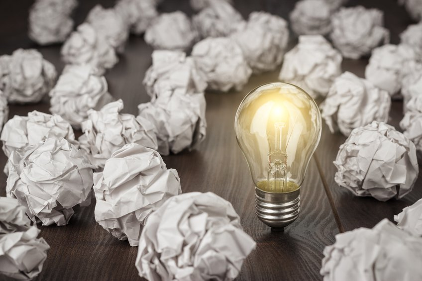 crumpled office paper and light bulb standing on the table