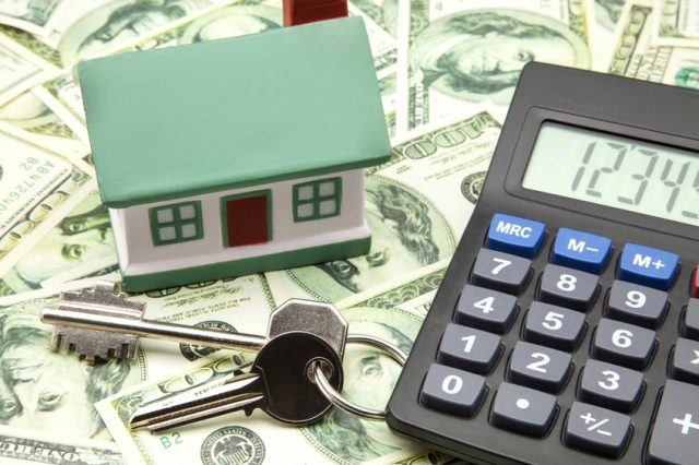 home model with calculator above dollar bills