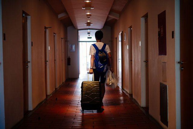 Man walking through a hotel with his bags