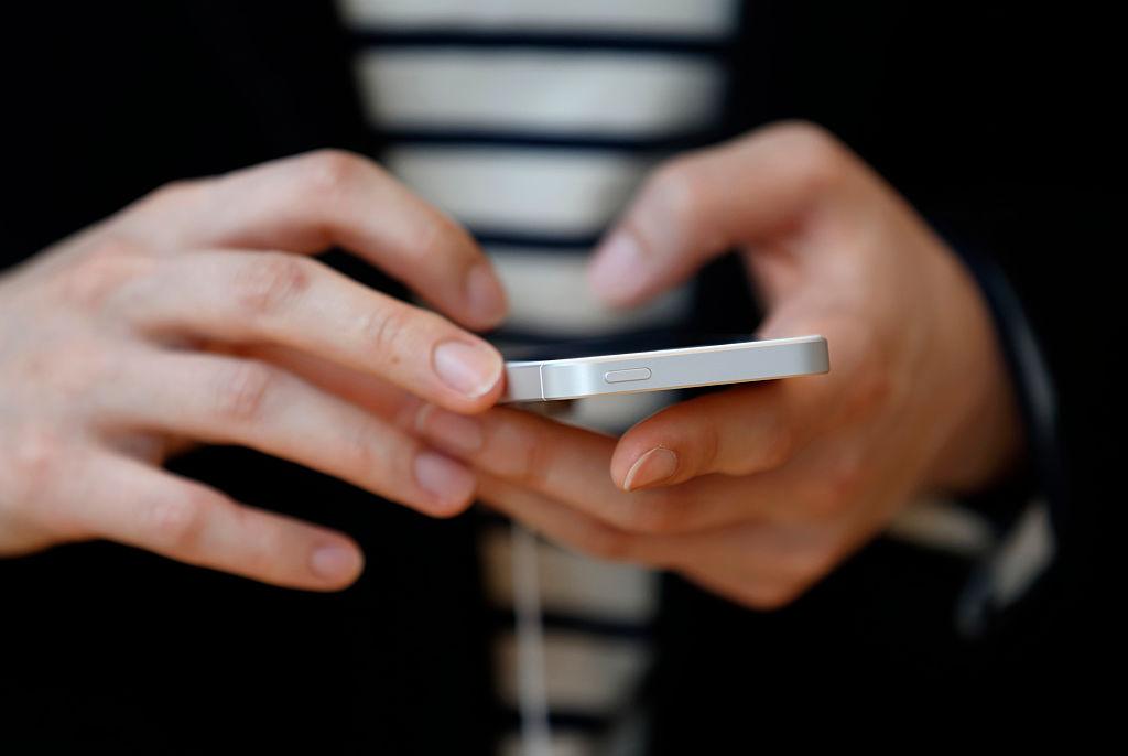 A customer tries an Apple Inc. iPhone SE