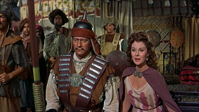 John Wayne as Genghis Khan in ancient military garb standing next to Susan Hayward as Bortai in The Conqueror