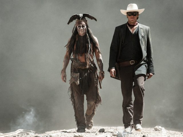 Johnny Depp as Tonto and Armie Hammer walk together with dust in the background in The Lone Ranger