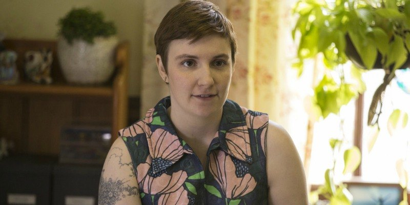 Lena Dunham is smiling in her Girls tv show.
