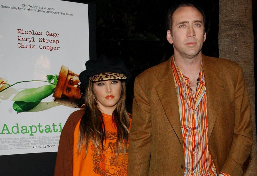 Lisa Marie Presley and Nicolas Cage looking at the camera, standing next to a poster for Adaptation
