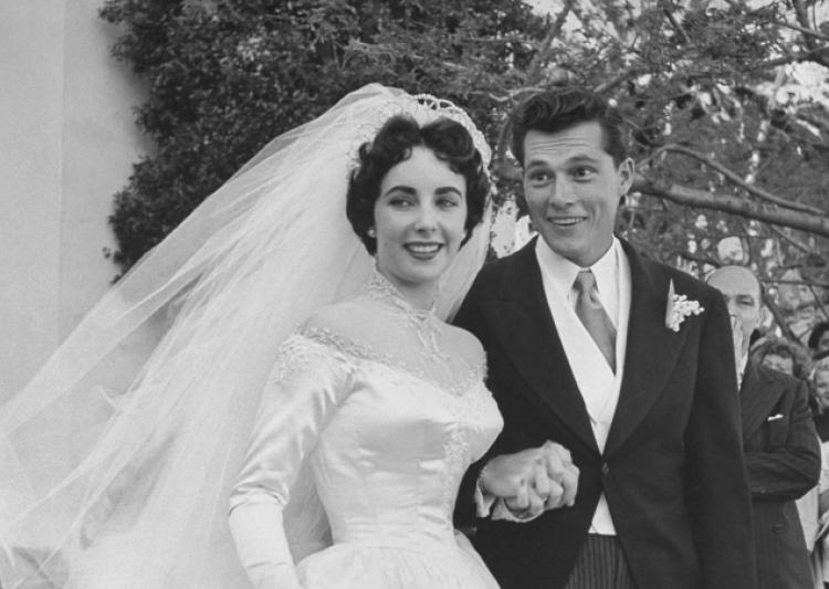 Elizabeth Taylor and Nicky Hilton after their wedding, holding hands and smiling for the camera