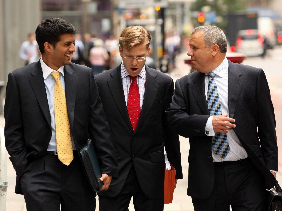 three men walking down the street in suits