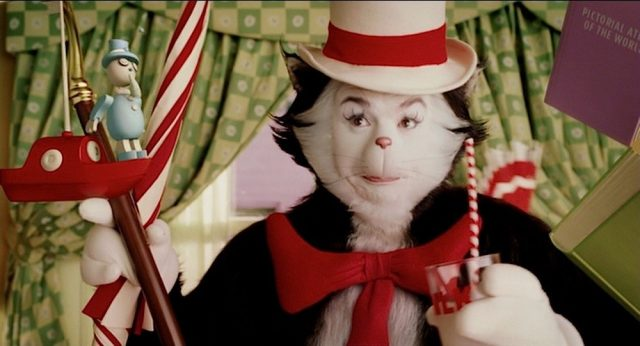 Mike Myers as the Cat in the Hat holding a toy boat on a hook and a cup with a straw
