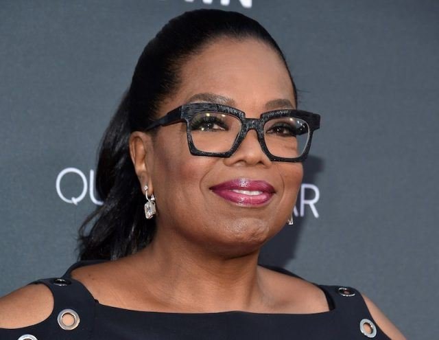 Oprah Winfrey smiling and wearing glasses while posing for photos at a red carpet event.