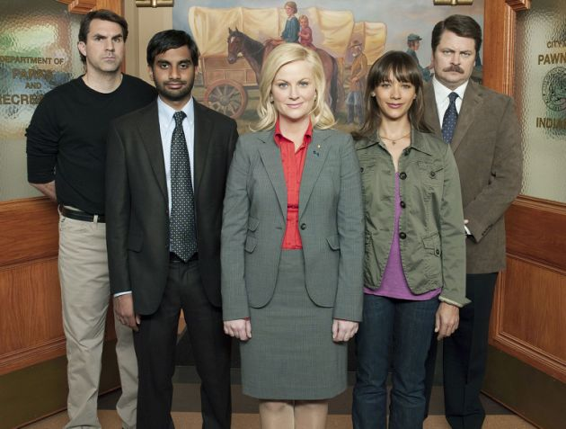 Paul Schneider, Aziz Ansari, Amy Poehler, Rashida Jones, and Nick Offerman stand next to one another in an office building on Parks and Rec