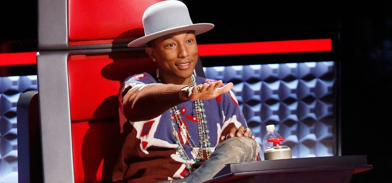 Pharrell with his hand up as if to push the button on The Voice.