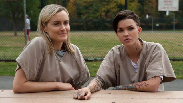 Taylor Schilling as Piper Chapman smiling and sitting a table with Ruby Rose as Stella looks annoyed