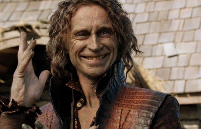Robert Carlyle as Rumplestiltskin smiling with his hand in the air on Once Upon a Time