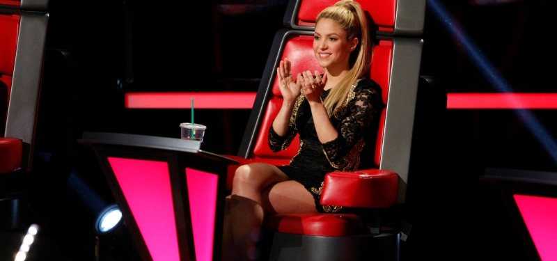 Shakira clapping and sitting in the coach' chair on The Voice.