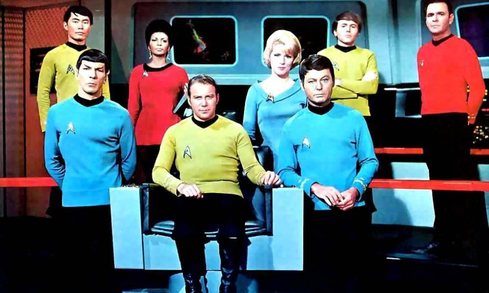The cast of Star Trek in yellow, blue, and red shirts sitting and standing