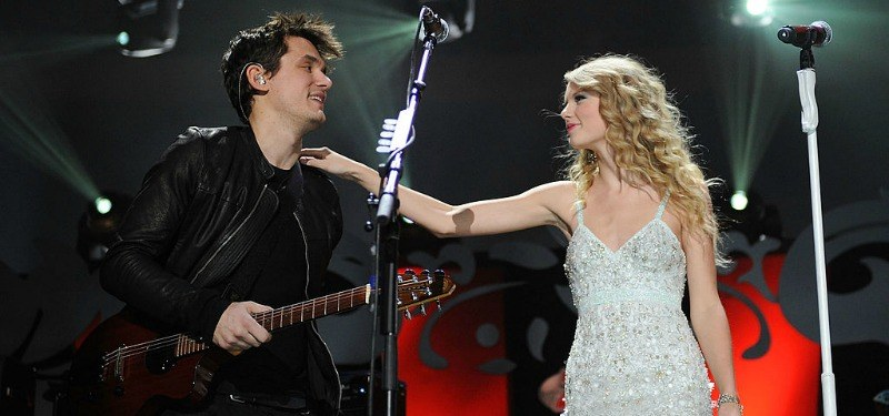 Taylor Swift has her hand on John Mayer's shoulder who is holding his guitar.
