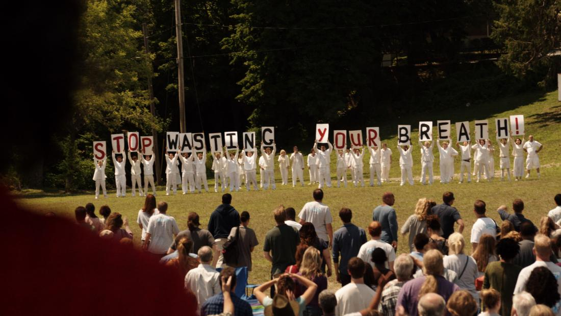 A group of protesters in white hold up signs that read Stop Wasting Your Breath in The Leftovers