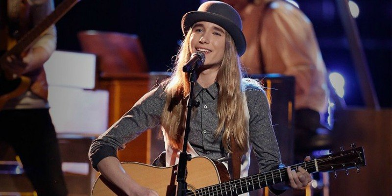 Sawyer Fredercks is singing on stage and playing his guitar on The Voice.