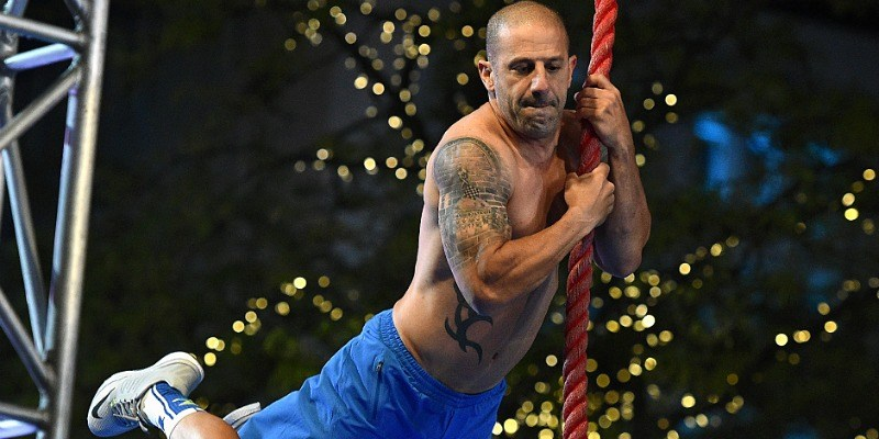 Tony Kanaan hangs from a rope on American Ninja Warrior
