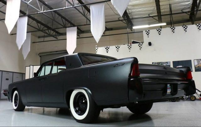 A black 1964 Lincoln Continental sits parked in a garage
