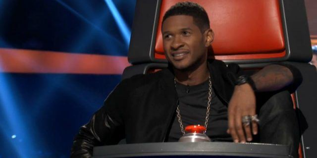 Usher listening in the coach chair on The Voice