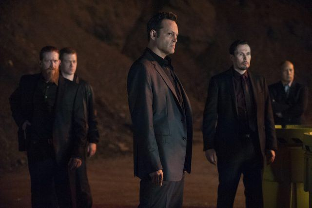 Vince Vaughn surrounded by men in black suits all looking angry on True Detective