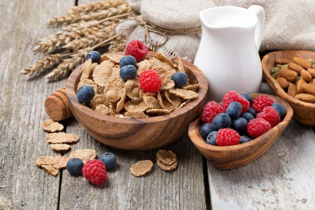 A wooden bowl full of whole grain cereal and fruits.