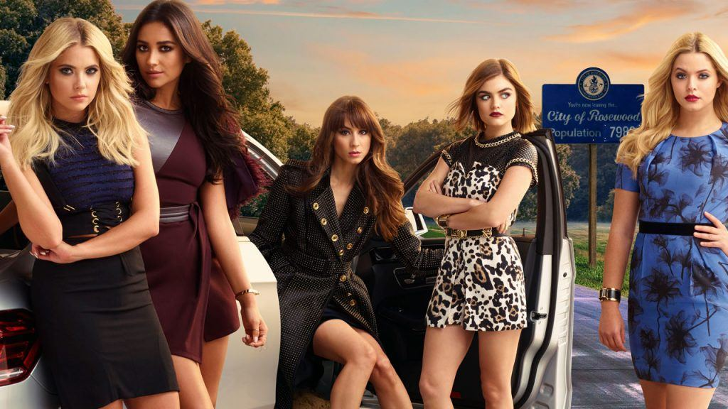 Troian Bellisario, Ashley Benson, Lucy Hale, Shay Mitchell, and Sasha Pieterse stand around a parked car in front of a Rosewood sign on Freeform's Pretty Little Liars